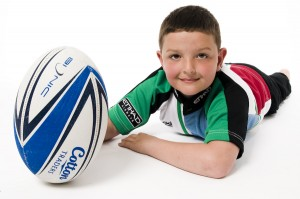 Boy holding a rugby ball taken in a portrait studio for a family photo shoot